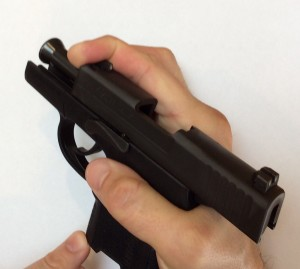 Sig P290 Field Stripping Instructions, Step 1: Pull the slide back with your index finger hooked around the end. Look for the slot in the slide to line up with the take down lever.
